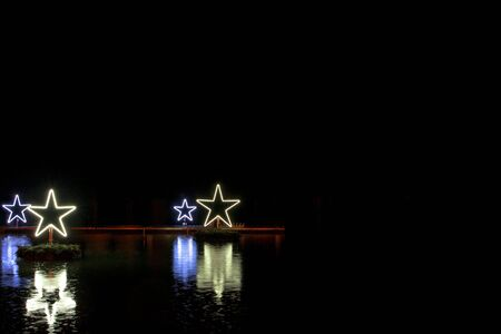Stars glowing blue and yellow on dark lake water, black background