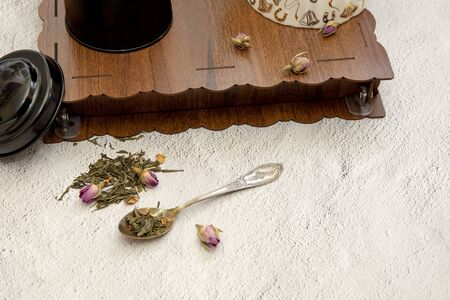 Dried green tea leaves with rose buds on spoon, light background Stockfoto