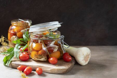 Colorful red and yellow cherry tomatoes in glass jar, woden cutting board and ingriedients on dark wooden background