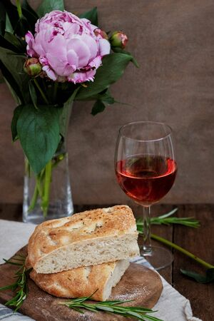 Focaccia bread on wooden table, wine, peony