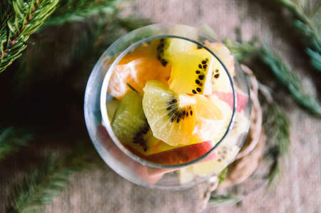 glass of fruit on a Christmas background with branches elomymi, Winter time