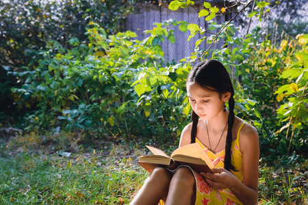 pretty teen girl reading a book in the garden Standard-Bild