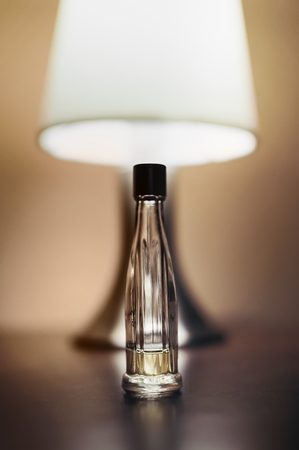 Table top lamp with burlap shade lit on a wooden table and a bottle of female perfume. Stock Photo