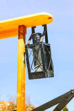 An ancient iron lantern, suspended on a wooden structure, was used on fire trucks in the old days.
