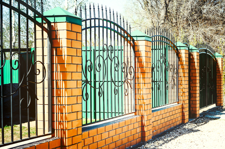 Brick and Metal Fence with Door and Gate of Modern Style Design Metal Fence Ideas. Stock Photo