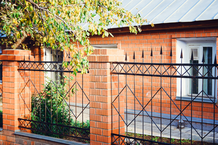 Metal fence with brick columns. A country house made of red brick.