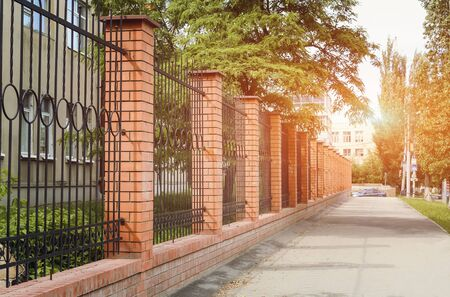 Brick and Metal Fence with Door and Gate of Modern Style Design In the setting sun. Metal Fence Ideas.