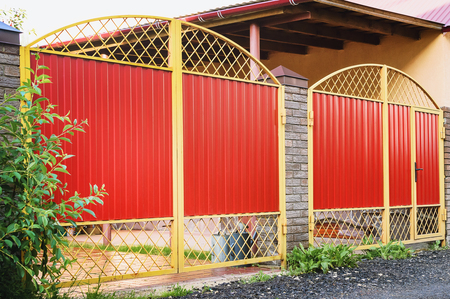 Metal red Fence with Door and Gate of Modern Style Design Metal Fence Ideas. Stock Photo
