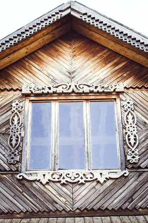 The old weathered wooden window with hinges and carved shutters. Retro. Stock Photo