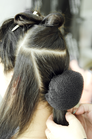 Closeup of a professional hairdressers hands doing a hairstyle in a beauty salon.