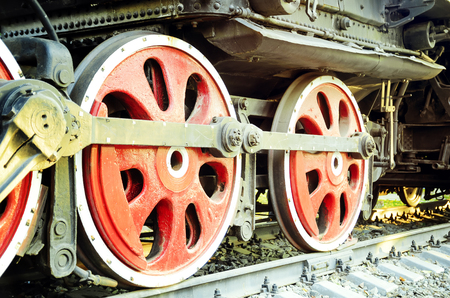 Train drive mechanism and red wheels of an old soviet steam locomotive. Stock Photo