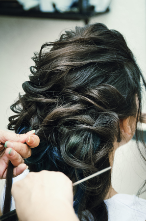 Closeup of a professional hairdressers hands doing a hairstyle in a beauty salon. Model brunette, in the hair some of the strands are painted blue. The concept of fashionable stylish hairstyle, professional work with hair.
