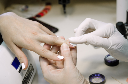 The master in gloves does a manicure in the salon, close-up.