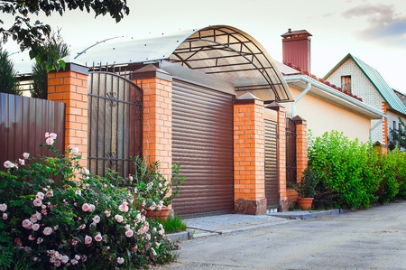 A brown fence made of polyprofile with a canopy in a modern style with brick columns, the design of a country house. Stock Photo