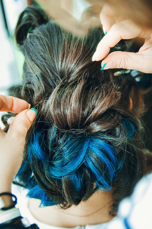Closeup of a professional hairdresser's hands doing a hairstyle in a beauty salon. Model of a brunette with long hair. The concept of fashionable stylish hairstyle, professional work with hair.