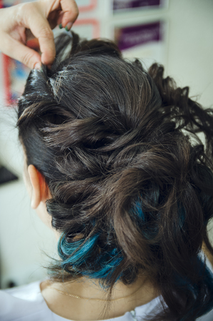 Closeup of a professional hairdressers hands doing a hairstyle in a beauty salon. Model of a brunette with long hair. The concept of fashionable stylish hairstyle, professional work with hair.