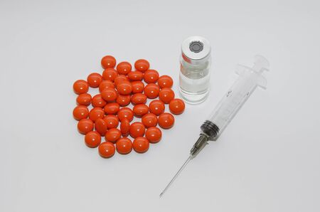A disposable medical syringe, ampoule and pills on a light background, close-up.