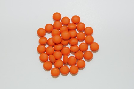 Many tablets in a protective shell of orange on a light background. Stock Photo