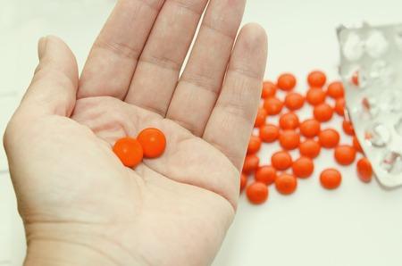 オレンジ シェルの 2 つの錠剤は、あなたの手の手のひらにあります。 写真素材