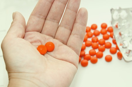 Two tablets in an orange shell lie on the palm of your hand.