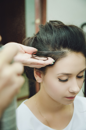 A professional hairdresser makes a festive hairstyle for the girl. Close-up.