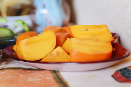 Fresh ripe persimmon, sliced on a plate. Closeup, selective focus.