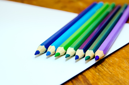 Colored pencils on a white sheet of paper. Close-up.