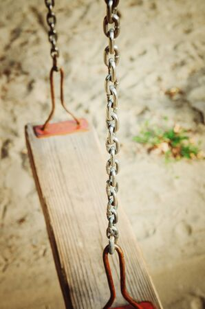 Old wooden swing on an iron chain. Stock Photo