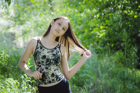 Beautiful teen girl brunette with long hair on a background of green trees.
