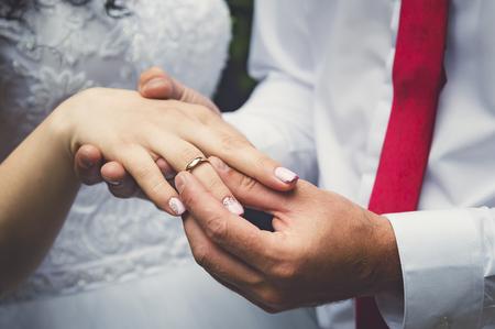 De bruidegom legt de ring aan de vinger van de bruid, handen close-up. Stockfoto