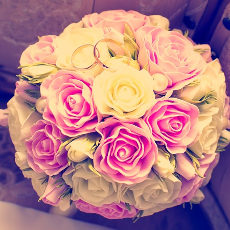 Gold wedding rings on a bouquet of pink flowers.