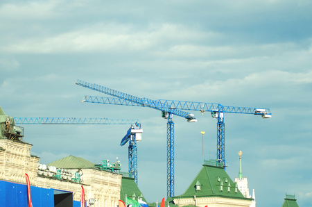 Construction cranes against the blue sky.