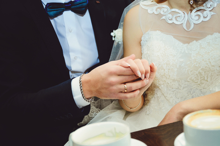 Young married couple holding hands, ceremony wedding day Close-up.