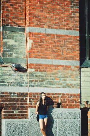 Beautiful girl with long dark hair on the brick wall background.