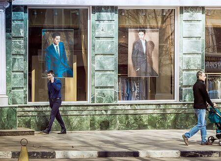 Saratov, Russia- April 26, 2015: Men walk down the street near the mens clothing store in Saratov. Redakční