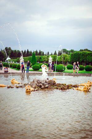 Saint Petersburg, RUSSIA - July 11, 2018: Tourists walk in Peterhof in St. Petersburg. Beautiful fountains, attractions.Vertical photo. Redakční