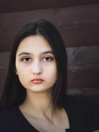 Portrait of a beautiful young girl with dark long hair and black eyes.