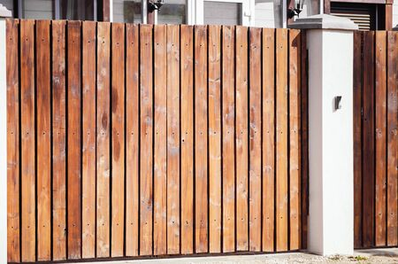Modern wooden fence with concrete pillars.