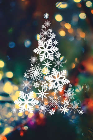 Abstract Christmas vertical background. Christmas tree made of snowflakes on a blurred background with lights.