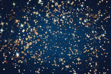 Golden sparkles, lights and decorative baubles on a dark blue background. Christmas background.