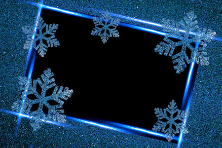 Blue decorative snowflakes on a black background in a frame. Space for text, copy-space.