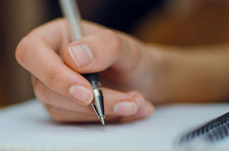 Close-up of a female hand writes.