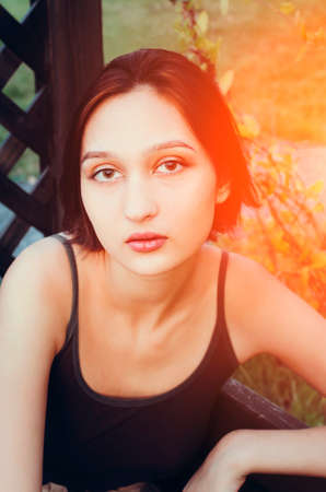 Beautiful young brunette is sitting outdoors in the park. Toning, vertical photography.