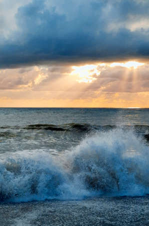 Sea waves in the rays of the setting sun. Vertical photography. Standard-Bild