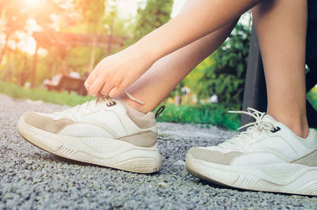 Girl tying laces on sneakers on the street, close-up. Sport active lifestyle concept. Close-up Standard-Bild
