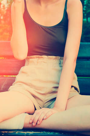 The girl is sitting on a bench in a relaxed casual position, close-up. Lifestyle concept. Vertical photography.