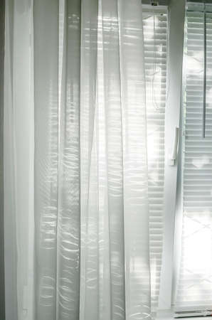 The window is closed with white blinds and a transparent organza curtain.