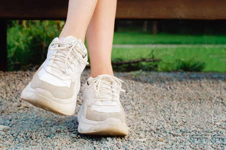 Legs of a young girl, shod in white sports sneakers, close-up.