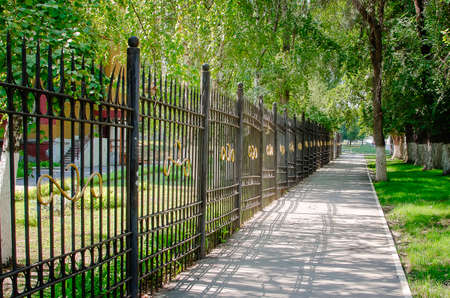 A beautiful forged metal fence along the alley in the city center.