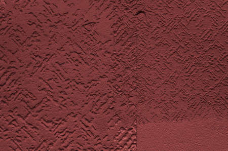 The texture of decorative plaster on the wall, burgundy color.